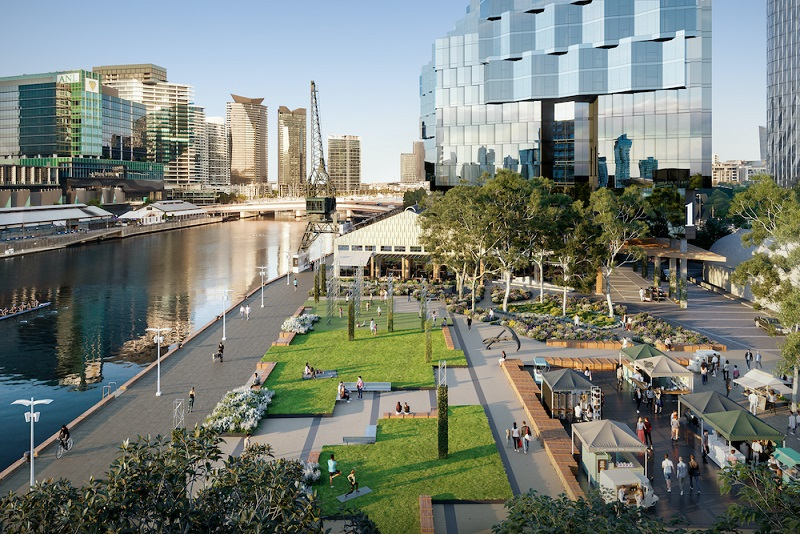 A park next to the river and hotel on the Yarra River shows a wide pathway, lawns and popup stores.