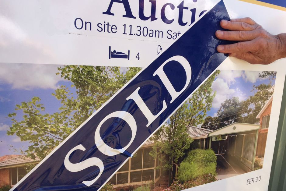 Auction sign on house replaced with sold sign.