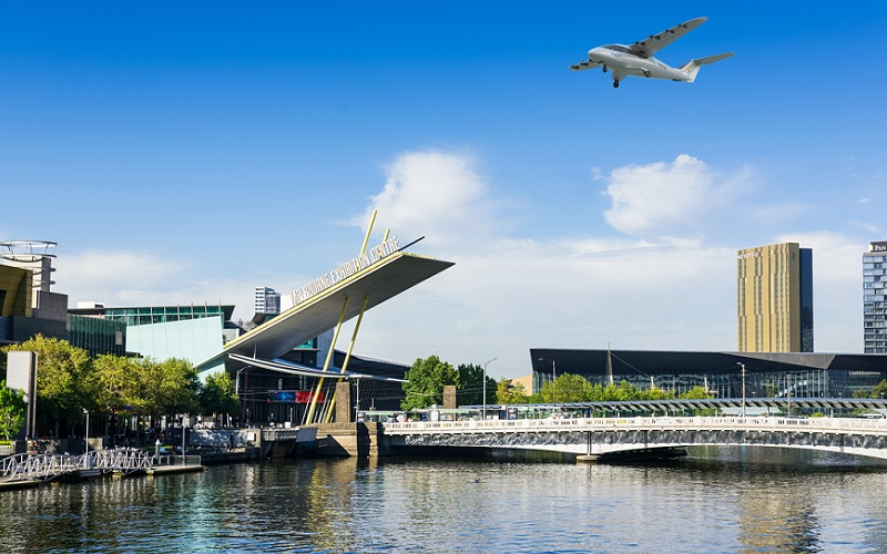 A small plane called an eSTOL flies over the Yarra River in Melbourne delivering passengers and freight.