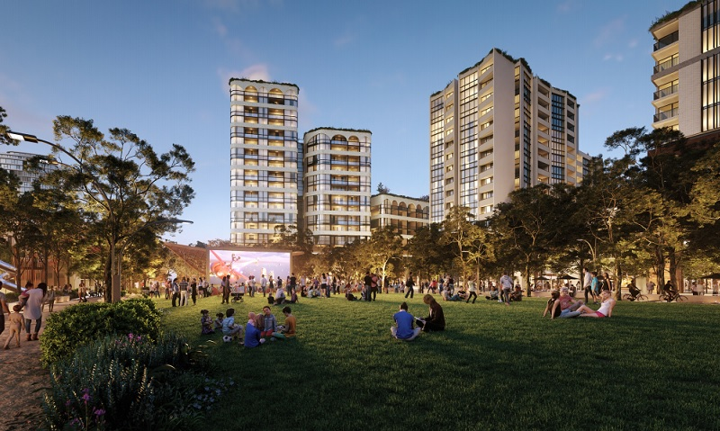 People sitting on a lawn watching an open air movie surrounded by 25-storey residential towers in Rouse Hill.