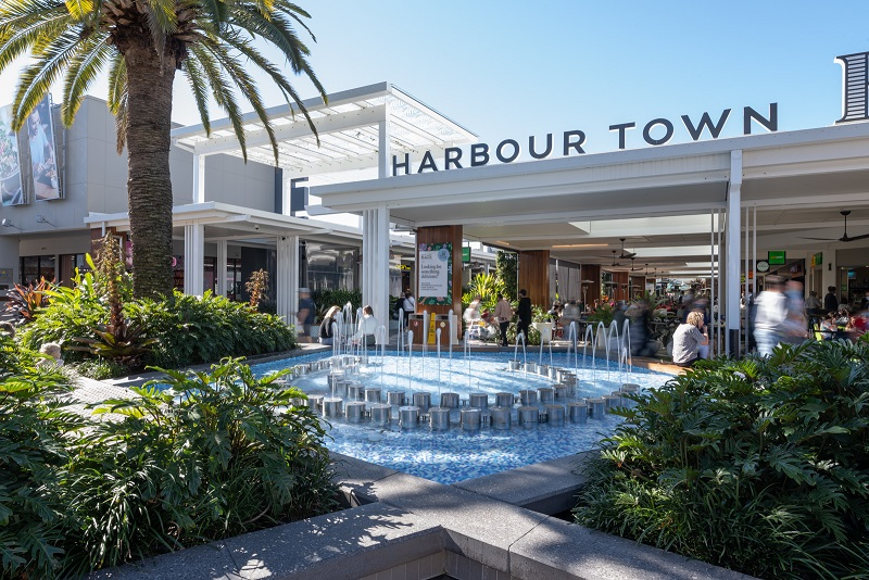 The blue fountain outside Harbour Town shopping centre on the Gold Coast is surrounded by shops and tropical plants.