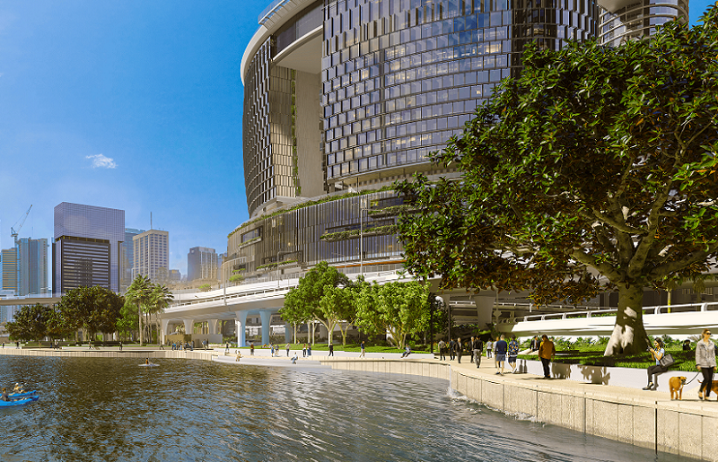 A park with mangrove trees along the Brisbane River in front of a large, round building with a hollow in the middle.