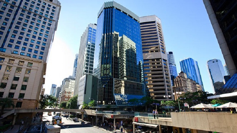 The 241 Adelaide Street of Brisbane Club Tower is a striking building on the corner of a busy street and lawn area.